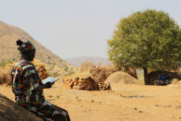 A woman reads a Bible in Sudan's Nuba Mountains.