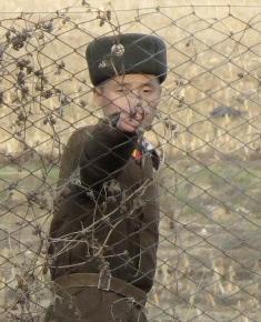 North Korean border guard at fence on Yalu Border between China and North Korea.