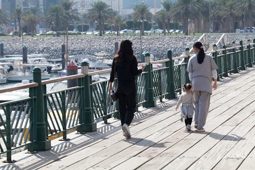 An Asian woman keeps close watch of a Kuwaiti girl as she walks a few steps ahead of her mother.
