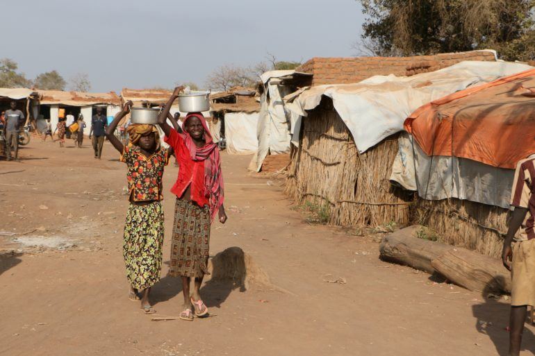 Teenage girls carry water in a refugee camp for people from the Nuba Mountains in Sudan. (Photo: World Watch Monitor)
